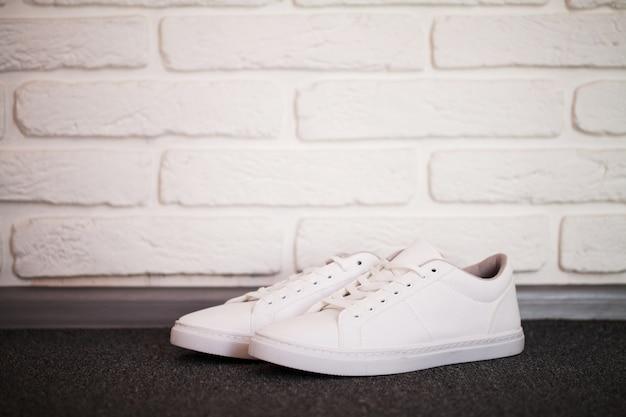 Paar nieuwe stijlvolle witte sneakers op vloer thuis. Premium Foto