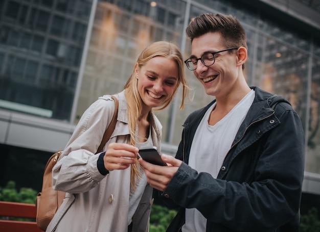 Paar of vrienden lachen grappig en plezier maken met een slimme telefoon in een grote straat in de stad. Premium Foto
