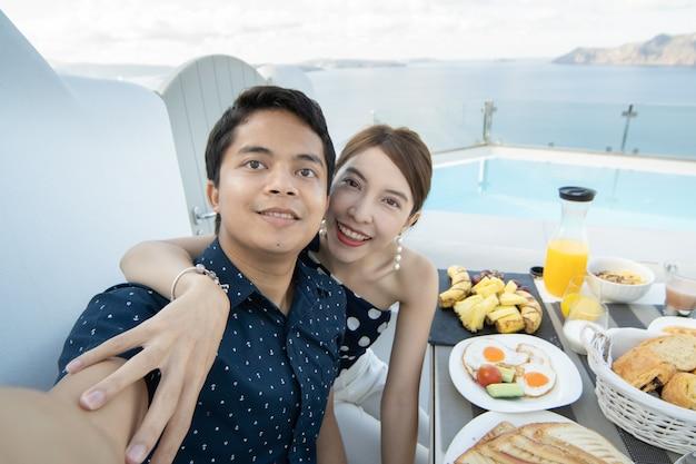 Paar ontbijten toerist nemen een selfie op terras hotel buiten Premium Foto