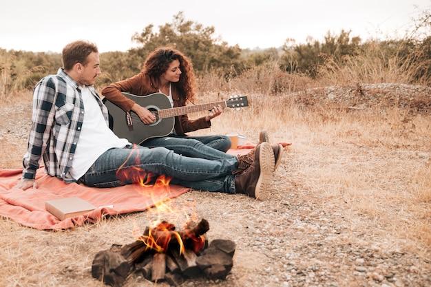 Paar ontspannen buiten naast een kampvuur Gratis Foto