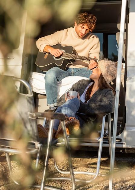 Paar ontspannen en gitaar spelen naast auto tijdens een road trip Gratis Foto