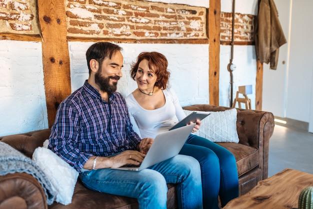 Paar ontspannen thuis in de bank op de computer en tablet Premium Foto
