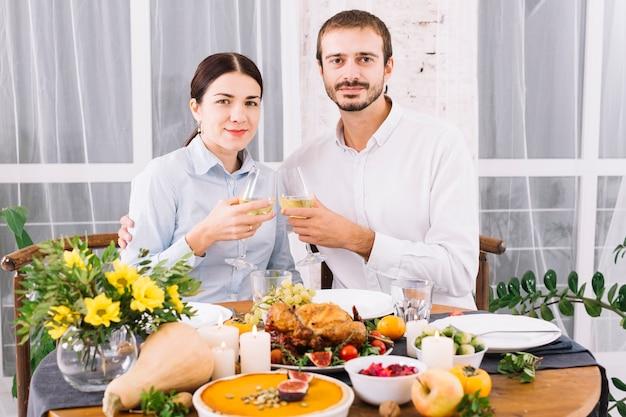 Paar rinkelende glazen aan feestelijke tafel Gratis Foto