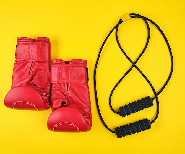 Paar rode lederen bokshandschoenen en zwarte trainer handexpander Premium Foto
