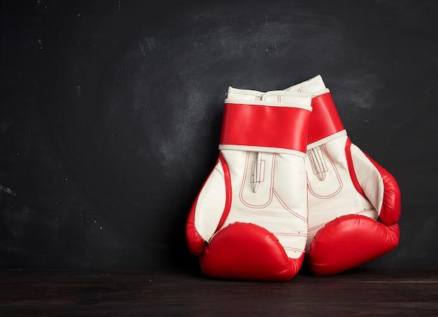 Paar rood-witte leer bokshandschoenen op een zwarte achtergrond, sportuitrusting Premium Foto