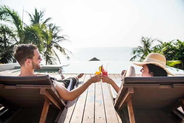 Paar roosteren met cocktails bij het zwembad Premium Foto