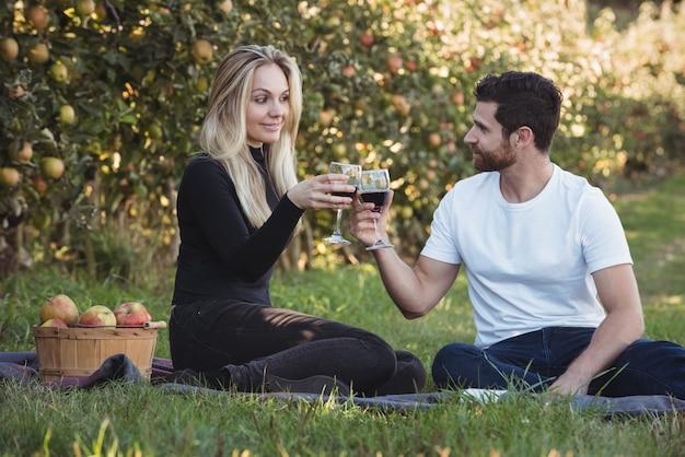 Paar roosterende glazen wijn in appelboomgaard Gratis Foto