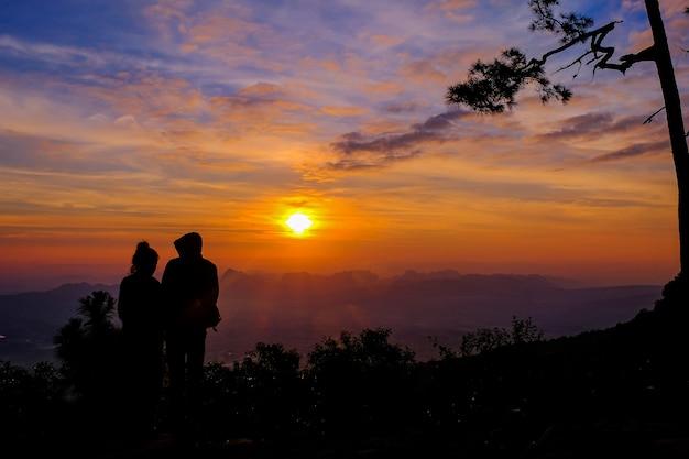 Paar silhouet op de top van een berg bij zonsondergang Premium Foto