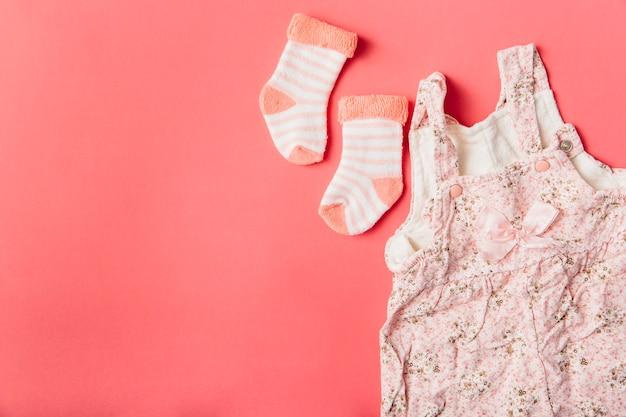 Paar sok en babykleding op felgekleurde achtergrond Gratis Foto