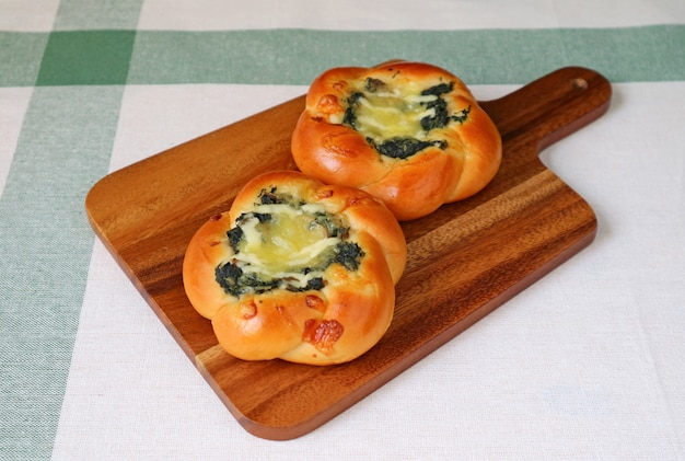 Paar spinazie en kaasbroodjes op een houten dienblad Premium Foto