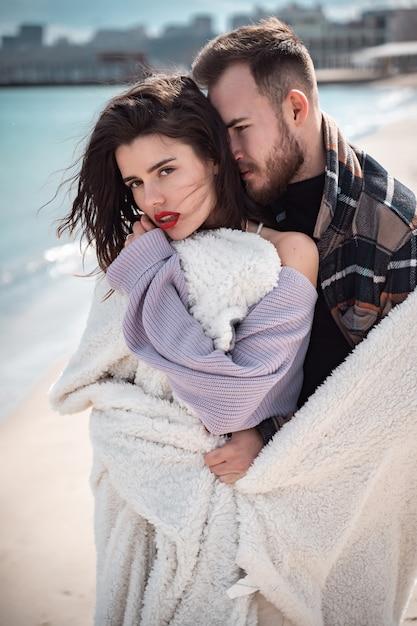 Paar staat op het strand en poseren Gratis Foto