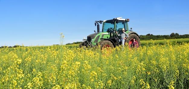 Paar van boeren in een koolzaad veld met een tractor Premium Foto