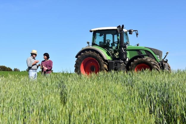 Paar van boeren in een tarweveld met een tractor Premium Foto