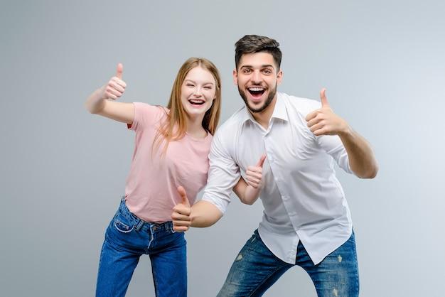 Paar van jonge man en vrouw die omhoog geïsoleerde duimen tonen Premium Foto