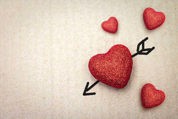 Paar van rood hart met cupidpijl op kartonachtergrond. Premium Foto