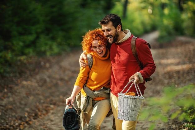 Paar verliefd knuffelen en wandelen in de natuur. het paar houdt picknickuitrusting vast. herfst tijd. Premium Foto