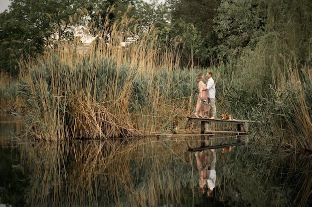 Paar verliefd knuffels en kussen op houten pier in de natuur. Premium Foto