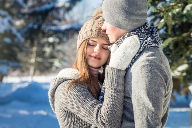 Paar verliefd knuffels in winter forest Premium Foto