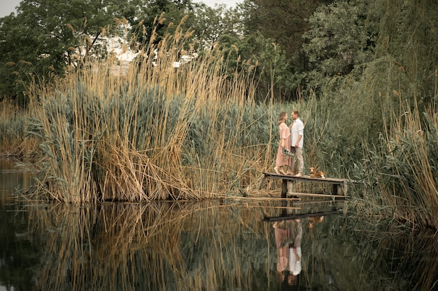 Paar verliefd knuffels op houten pier op aard. Premium Foto