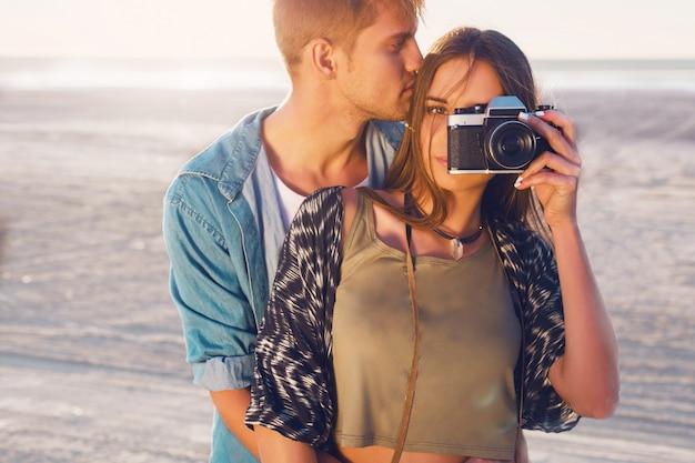 Paar verliefd poseren op het strand van de avond, jonge hipster meisje en haar knappe vriendje fotograferen met retro filmcamera. warm licht bij zonsondergang. Gratis Foto
