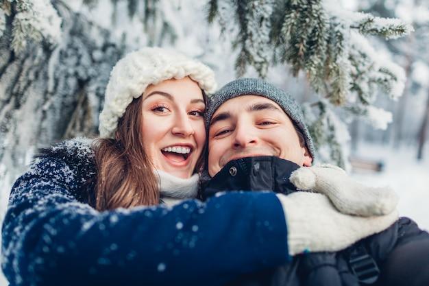 Paar verliefd selfie te nemen en knuffelen in winter forest. jonge gelukkige mensen plezier. Premium Foto