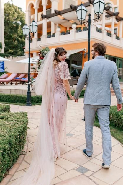Paar verliefd wandelen in luxevilla tijdens het vieren van bruiloft. volledige lengte. Gratis Foto