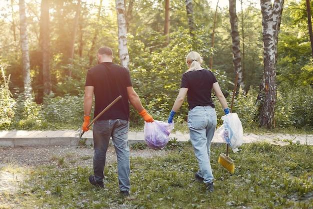 Paar verzamelt afval in vuilniszakken in park Gratis Foto