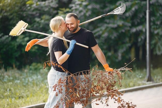 Paar verzamelt bladeren en maakt het park schoon Gratis Foto