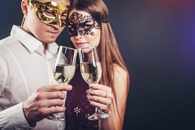 Paar vieren oudejaarsavond drinken champagne op maskerade partij Premium Foto