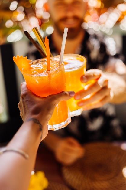 Paar vrienden rammelende glazen smakelijke tropische cocktails op zonnige dag in café Gratis Foto