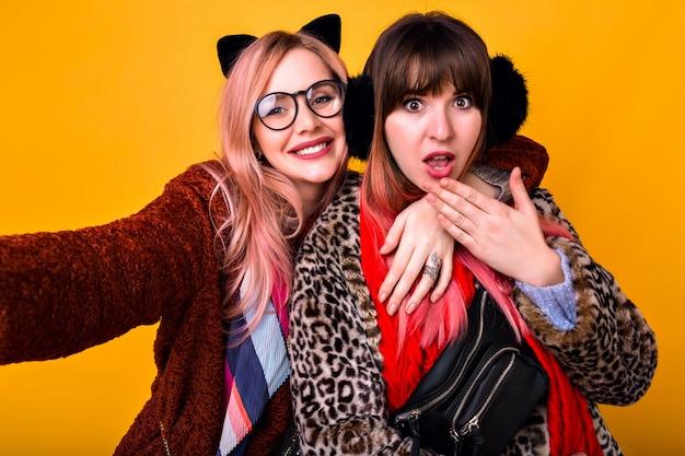 Paar vrij grappige hipster beste vrienden zus meisjes selfie maken op gele muur, tong tonen en glimlachen, trendy lente bedrukte bontjassen, sjaals, heuptasje en heldere bril dragen. Gratis Foto