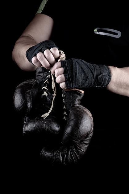 Paar zeer oude bokssporthandschoenen in handen van mannen Premium Foto
