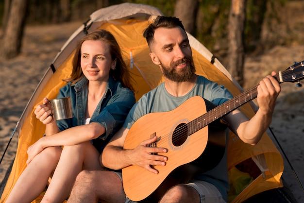 Paar zingen en drinken op de camping Gratis Foto