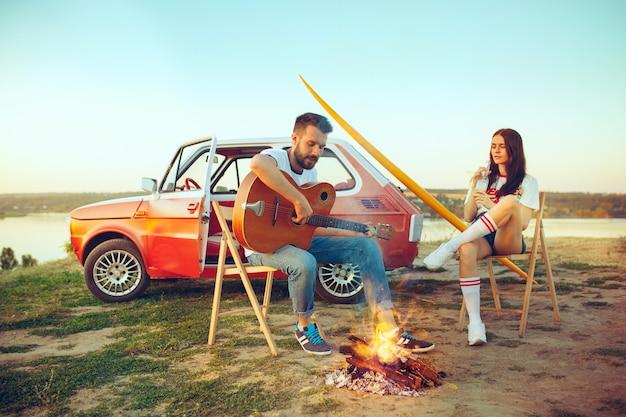 Paar zitten en rusten op strand gitaar spelen op een zomerdag in de buurt van de rivier Gratis Foto