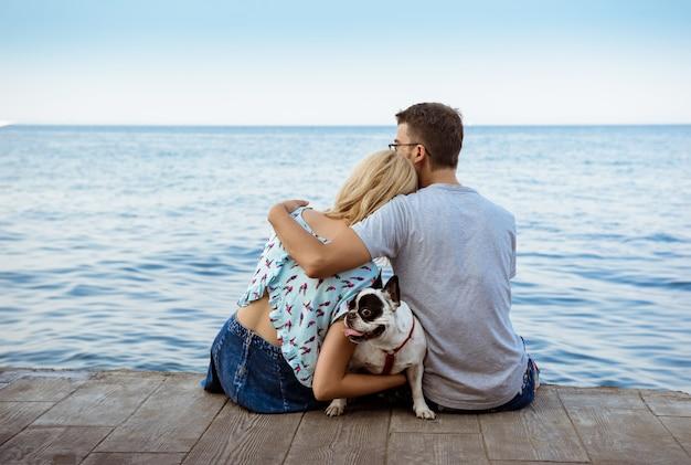 Paar zitten met franse bulldog in de buurt van de zee Gratis Foto