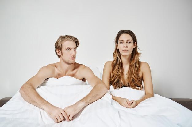 Paar zittend in bed onder deken met problemen in de slaapkamer uiting geven aan teleurstelling paar had ruzie in de ochtend en moment van romantiek geruïneerd. beiden willen niet eerst hun excuses aanbieden. Gratis Foto