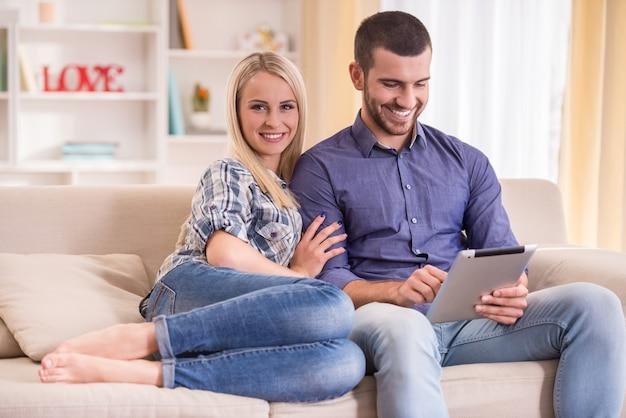 Paar zittend op de bank thuis, met behulp van een tablet. Premium Foto