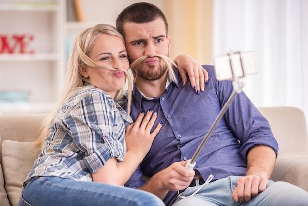 Paar zittend op de bank thuis, met behulp van telefoon. Premium Foto