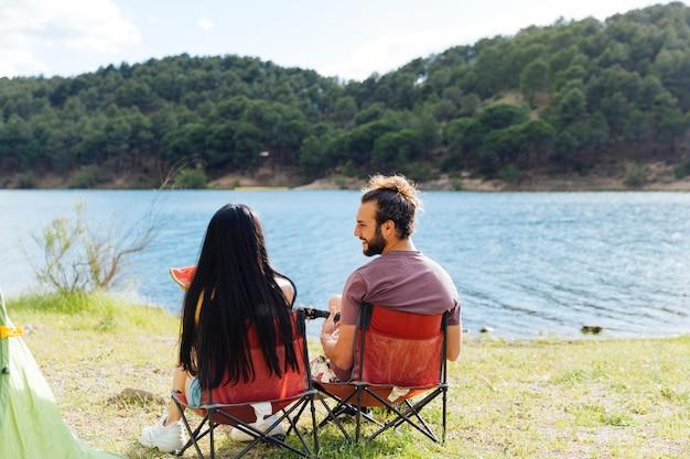 Paar zittend op de rivieroever samen Gratis Foto