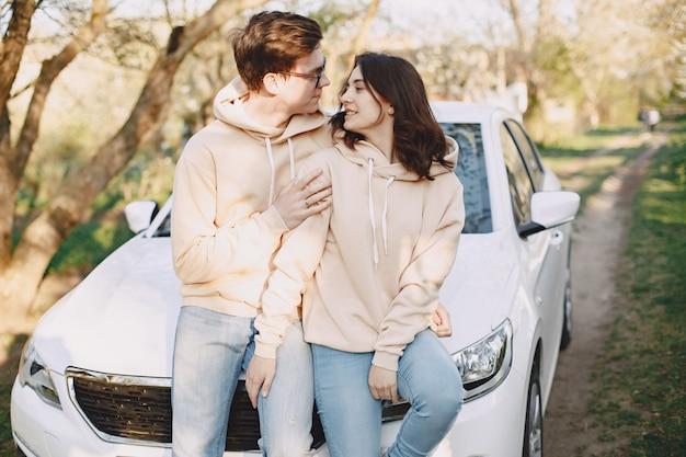 Paar zittend op een motorkap van auto in een park Gratis Foto
