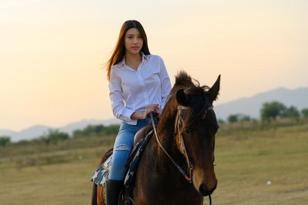 Paardrijden van achteren met uitzicht op wijd open veld en bergen Premium Foto