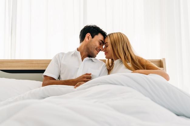 Paarminnaar die het witte het glimlachen gelukkige spelen samen op bed dragen vroege ochtend Premium Foto
