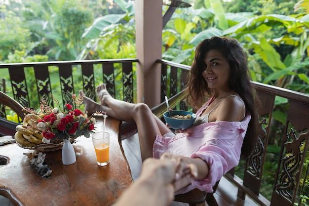 Paarontbijt, glimlachende vrouw die muesli eten en sinaasappelsap drinken Premium Foto