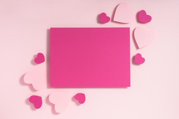 Paars en roze harten blanco vel papier op pastel roze achtergrond Premium Foto