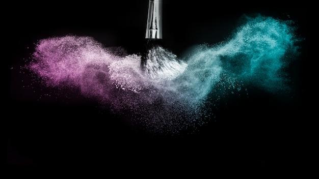 Paarse en blauwe oceaanpoeder kleurenplons en borstel voor make-upkunstenaar Premium Foto