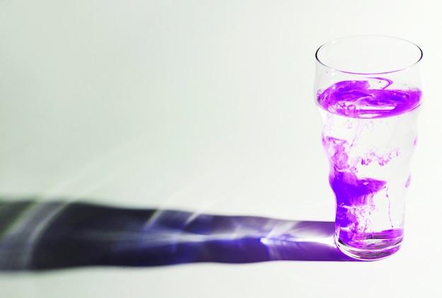 Paarse inkt lossen op in een glas water met schaduw op witte achtergrond Gratis Foto
