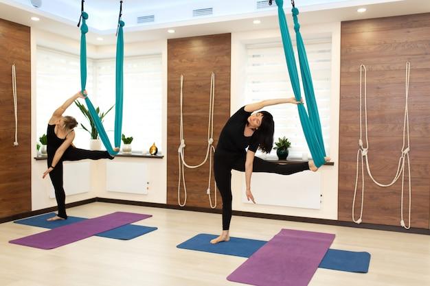 Paarvrouw die uitrekkende oefeningen van de vliegyoga in gymnastiek doen Premium Foto