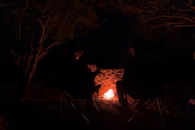 Paarzitting bij brandend kampvuur in de nacht. namibië, afrika. zomeravonturen Premium Foto