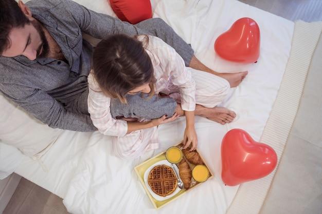 Paarzitting op bed met voedsel op dienblad Gratis Foto
