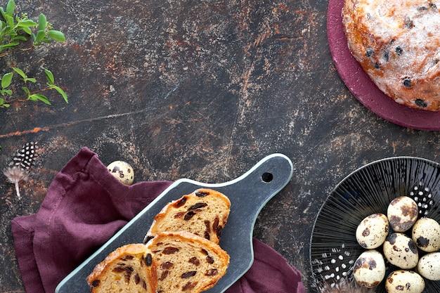 Paasbrood (osterbrot in het duits). bovenaanzicht van traditionele fruitige brood op donkere tafel met verse bladeren en kwarteleitjes. kopie-ruimte. Premium Foto